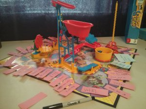Mouse trap game with sticky notes on spaces.